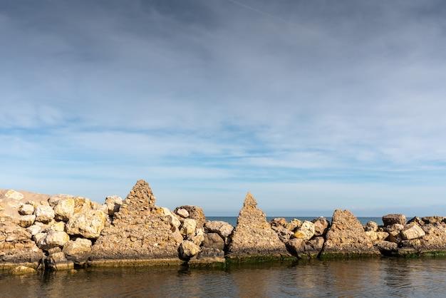 Costruzioni piramidali di frangiflutti alla foce di un fiume fino al mare.