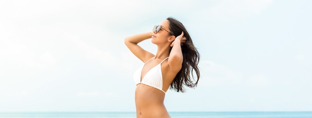 Costume da bagno bianco da portare della bella donna asiatica sul fondo dell'insegna della spiaggia di estate