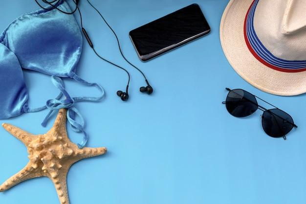 Costume da bagno bikini, cappello, telefono, occhiali da sole e stelle marine su blu