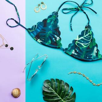 Costume da bagno bikini tropicale, moda da spiaggia. accessori donna viaggiatore piano laici con costumi da bagno, foglie di palma.