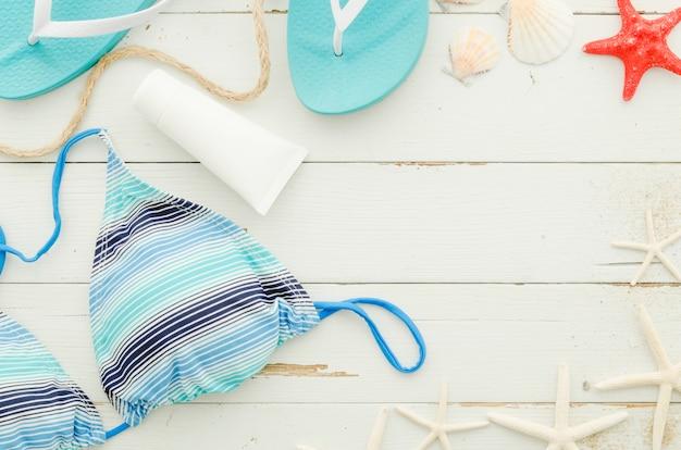 Costume da bagno con crema solare e stelle marine