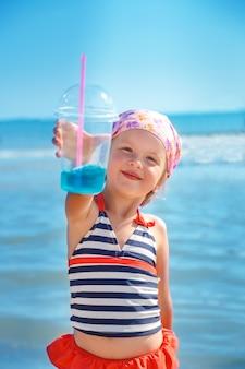 Costume da bagno felice della bambina con il cocktail blu sulla spiaggia. estate. vacanza. mare. oceano.