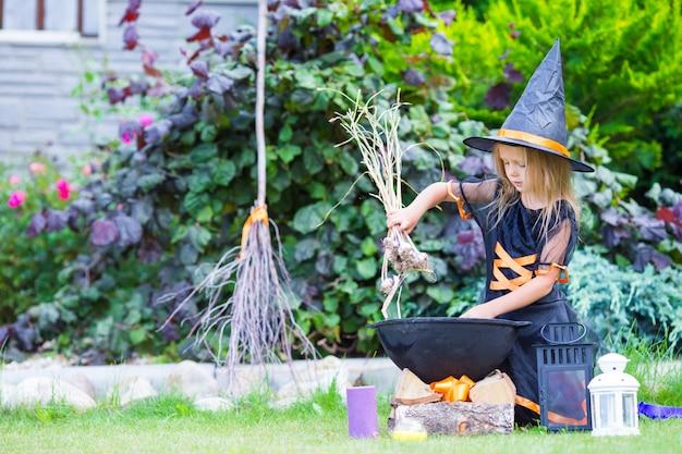 Costume da portare della strega della bambina adorabile con la scopa su halloween all'aperto
