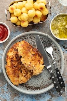 Cotoletta alla milanese con polpette di patate e salsa al limone. cotoletta di pollo impanata