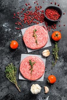 Cotoletta di carne macinata cruda, carne macinata di manzo e maiale. polpette di hamburger sul nero. vista dall'alto