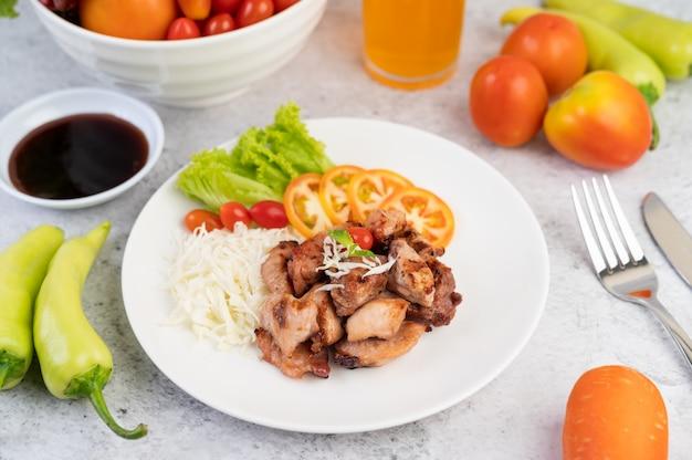 Cotoletta di maiale alla griglia con pomodori e insalata, disposti in un piatto bianco.