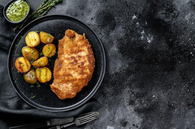 Cotoletta di pollo fritto con patate al forno. superficie nera. vista dall'alto. copia spazio
