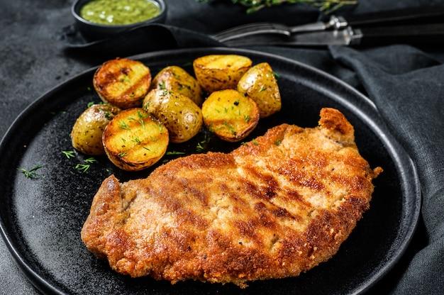 Cotoletta di pollo fritto con patate al forno. superficie nera. vista dall'alto