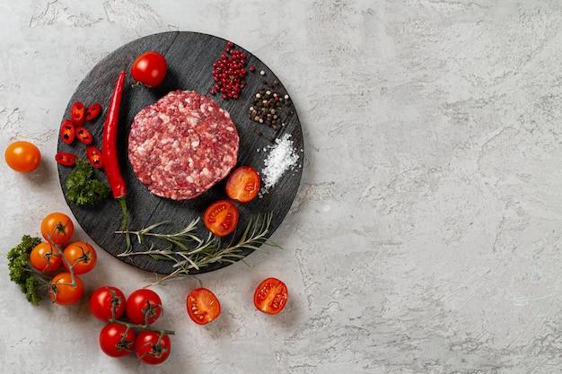 Cotoletta fatta in casa cruda fresca con spezie e pomodori sul tavolo