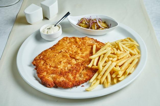 Cotoletta fritta con patatine fritte, salse e insalata su un piatto bianco. ristorante che serve cibo. disteso