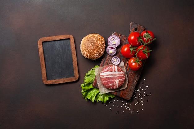 Cotoletta, pomodori, lattuga, panino, formaggio, cetrioli e cipolla crudi degli ingredienti dell'hamburger su fondo arrugginito