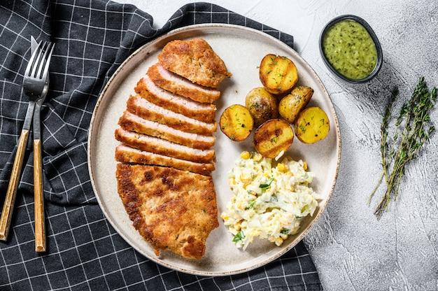 Cotoletta tedesca impanata casalinga del weiner con le patate e l'insalata.