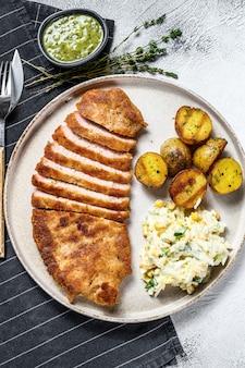 Cotoletta viennese impanata con patate al forno e insalata. superficie grigia. vista dall'alto