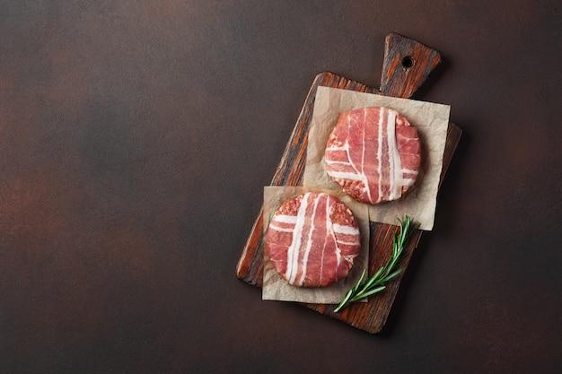 Cotolette crude dell'hamburger con i rosmarini sul tagliere e sul fondo arrugginito