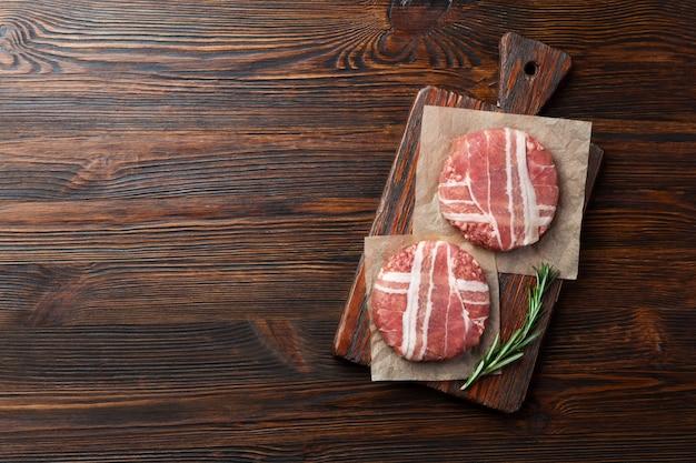 Cotolette crude dell'hamburger con rosmarino sul tagliere e sulla tavola di legno