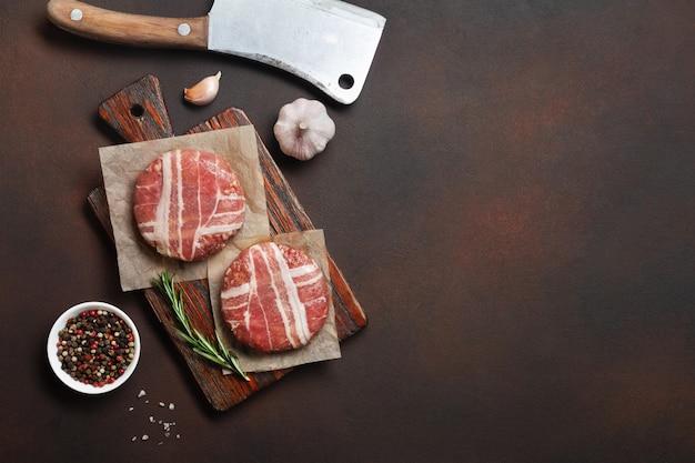 Cotolette crude dell'hamburger con rosmarino sul tagliere