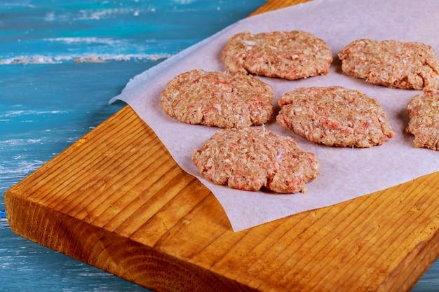 Cotolette crude della bistecca dell'hamburger della carne della carne macinata con condimento sui bordi di legno d'annata
