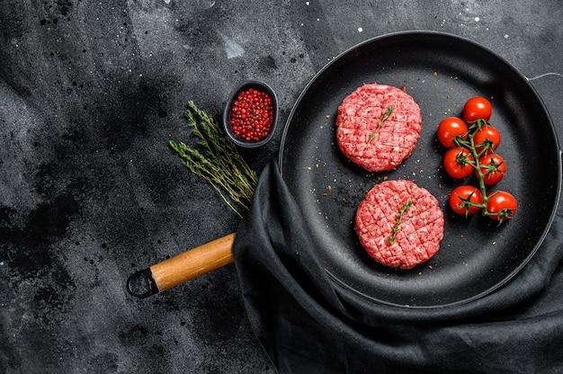 Cotolette crude della bistecca dell'hamburger della carne della carne tritata in una pentola. superficie nera. vista dall'alto. copia spazio