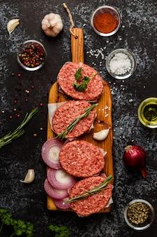 Cotolette crude della bistecca della carne tritata con le erbe e le spezie