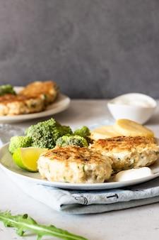 Cotolette deliziose (pesce o carne) con broccoli, patate e salsa su un piatto.