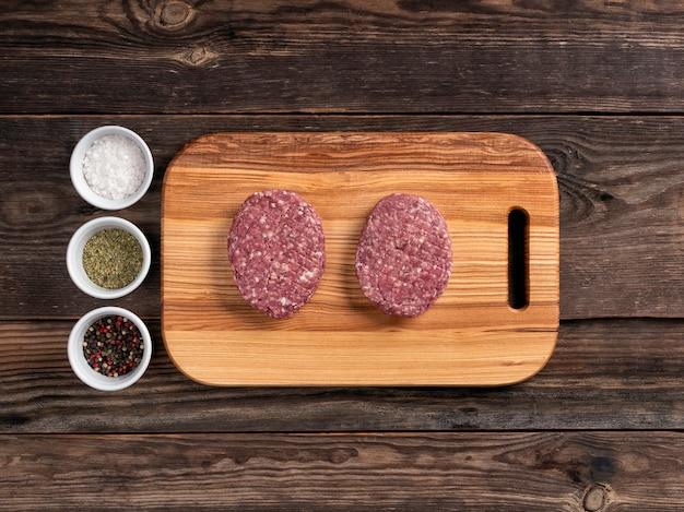 Cotolette di carne cruda per hamburger sul tagliere di legno. disteso.