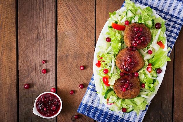 Cotolette di carne succosa con salsa di mirtilli e insalata su un tavolo di legno in stile rustico. vista dall'alto
