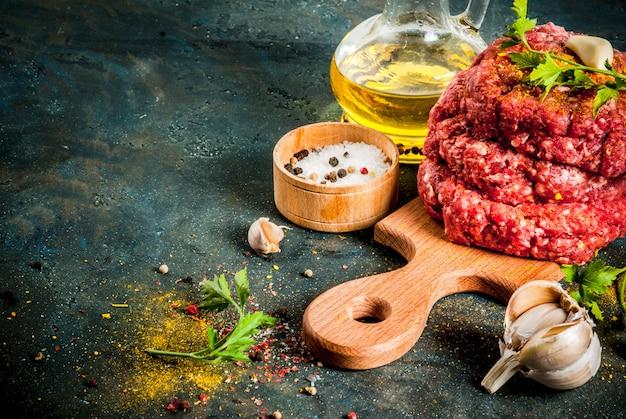 Cotolette di hamburger crudo con sale, pepe, olio, erbe e spezie, sul tavolo scuro, copia spazio vista dall'alto