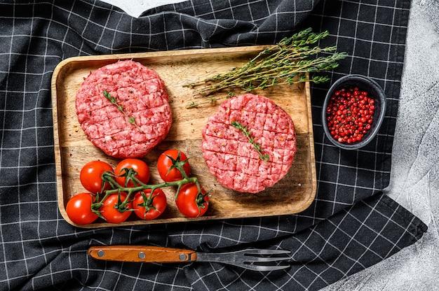 Cotolette di hamburger di carne macinata. superficie grigia. vista dall'alto