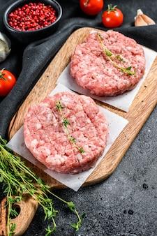 Cotolette di maiale crudo, tortino di carne macinata su un tagliere. trito biologico. vista dall'alto