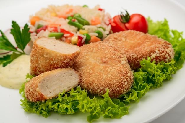 Cotolette di pollo in pastella con risotto e verdure