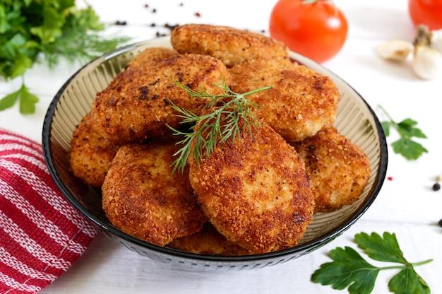 Cotolette fatte in casa succose (manzo, maiale, pollo) su un fondo di legno bianco.