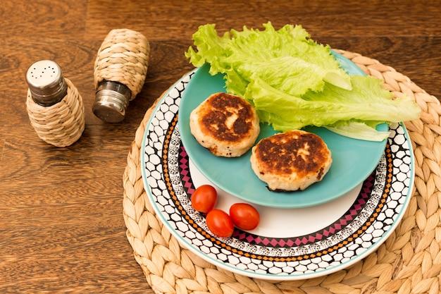 Cotolette fatte in casa succose (manzo, maiale, pollo) su un fondo di legno.