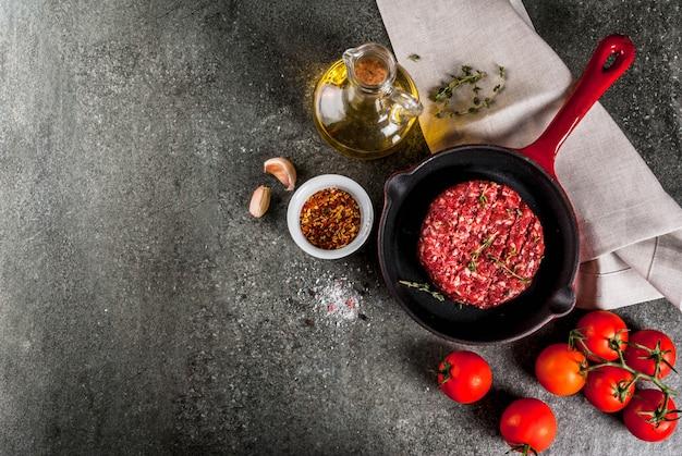Cotolette organiche crude degli hamburger della carne del manzo con le spezie, timo, pomodori, olio d'oliva in padella sul copyspace nero e di vista superiore