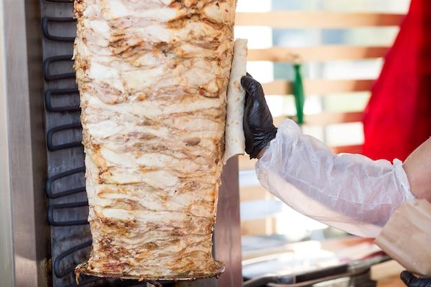 Cottura del kebab turco del doner. lo chef lubrifica il pane pita con il grasso della carne.