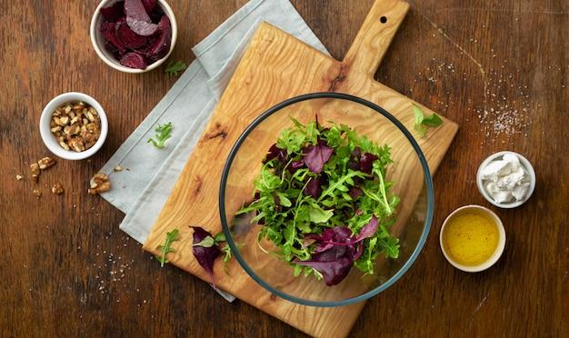 Cottura dell'insalata fresca sulla tavola di legno