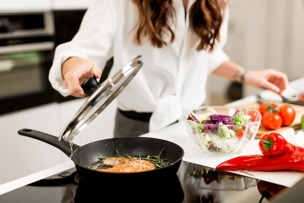 Cottura della bistecca di pesce con verdure e spezie su una padella in cucina. cibo sano e nutrizione