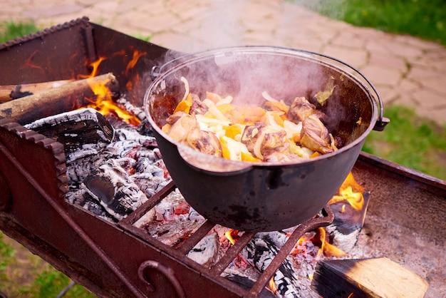 Cottura di carne con verdure sul fuoco.
