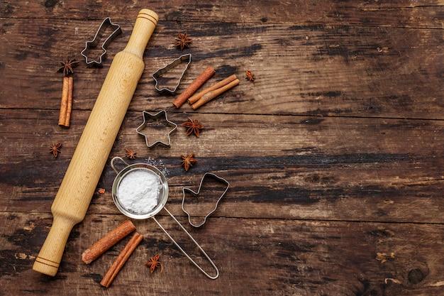 Cottura natalizia, prodotti da forno, spezie, formine per biscotti - stelle, angelo e abete, setaccio, zucchero a velo e mattarello. vecchie tavole di legno