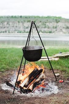 Cottura pentola che incombe su legna da ardere ardente
