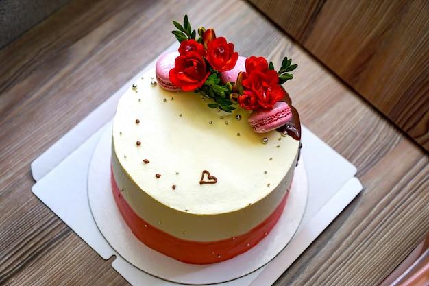 Cottura torta meravigliosamente avvolta con un grande fiocco. pan di spagna decorato con fiori freschi e biscotti