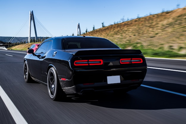 Coupé sportivo nero guida con luci rosse posteriori accese.