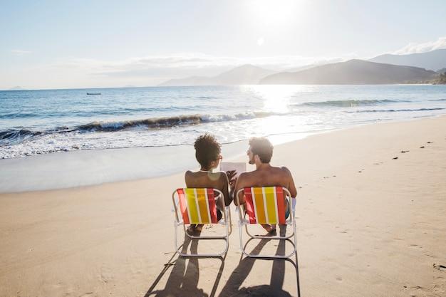 Couple chilling su sedie a sdraio con in spiaggia