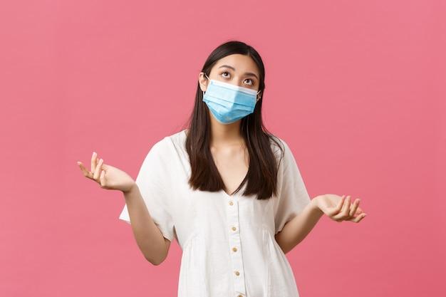 Covid-19, distanza sociale, concetto di virus e stile di vita. giovane donna asiatica indecisa e titubante in maschera medica, scrollando le spalle e alzando lo sguardo dubbiosa, soppesando le scelte, in piedi muro rosa