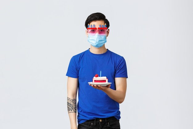 Covid-19 e concetto di lifestyle. il giovane ragazzo riluttante asiatico in vetri divertenti che tengono la torta di compleanno senza emozioni, l'odio celebra a casa durante la pandemia