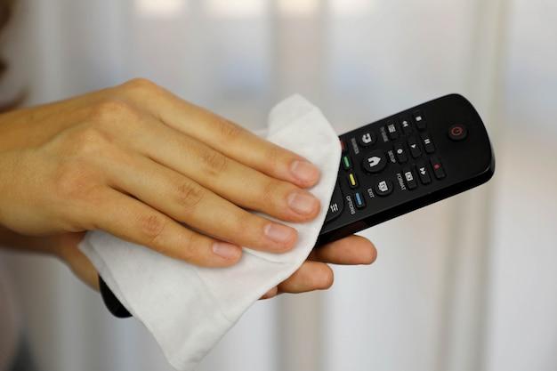 Covid-19 pandemia coronavirus donna che pulisce con salviettine umidificate telecomando tv disinfetta contro la malattia da coronavirus 2019 focolaio