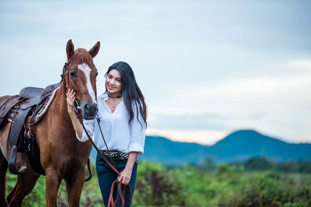 Cowgirl che guida su una montagna con un cielo giallo