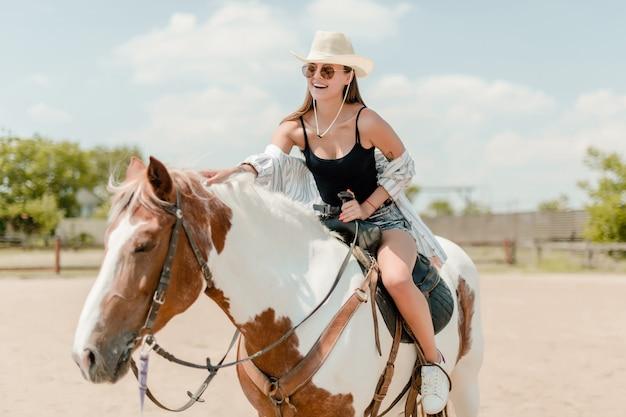 Cowgirl della campagna che monta un cavallo in un ranch