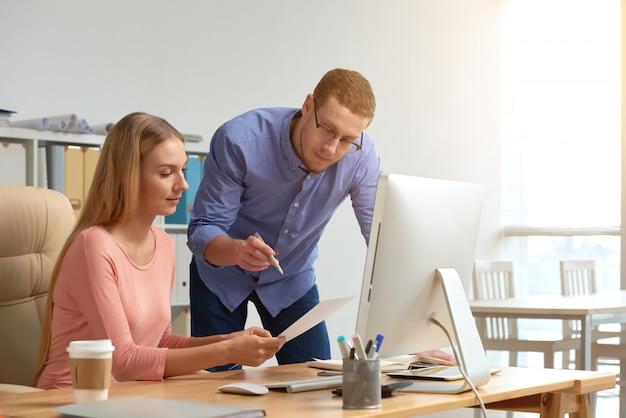 Coworking della donna e dell'uomo sul documento di affari che genera le idee