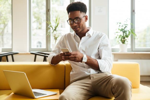 Coworking di seduta sorridente del giovane uomo africano che chiacchiera dal telefono.