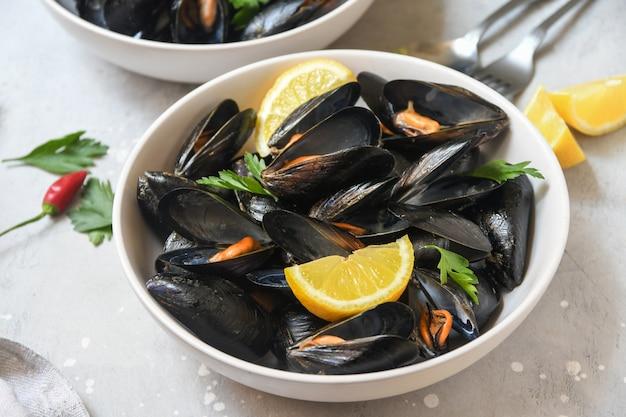 Cozze ai frutti di mare con piatto di limone e prezzemolo